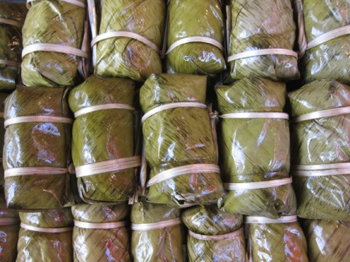 packages of sticky rice with red bean wrapped in banana leaf