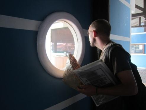 Richie peeping through the window at the Bali Marina as our boat-dreams sail away
